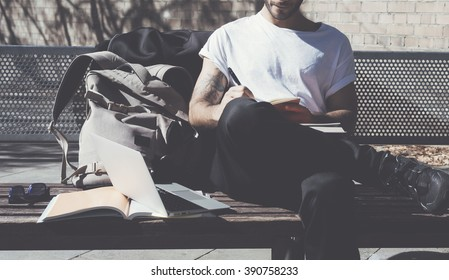 Student wearing white tshirt sitting city park and writes message. Studying at the University, working project. Books, generic design laptop, backpack bench. Wide