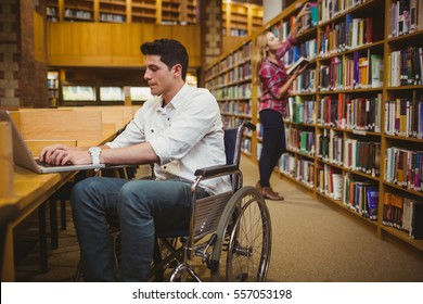 Student in wheelchair typing on his laptop while woman searching books in library