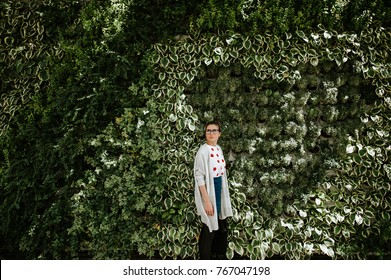 Student woman in the city in front of a wall covered with plants in modern city.