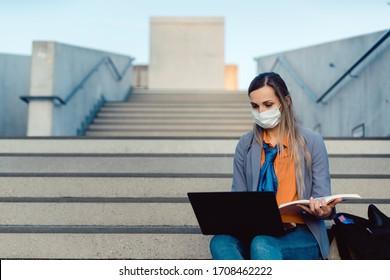 Studentenfrau, die auf leeren Stufen auf dem Universitätscampus sitzt
