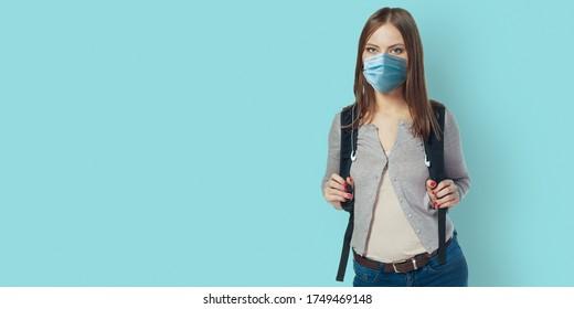 Studentin, die eine Gesichtsmaske trägt, die auf der blauen Wand mit Rucksack steht. Sicher zurück zur Schule während der Pandemie-Konzept. Neue normale Schulbildung.