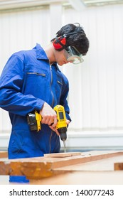 Student of a woodworking class learning to drill with nails in wooden boards