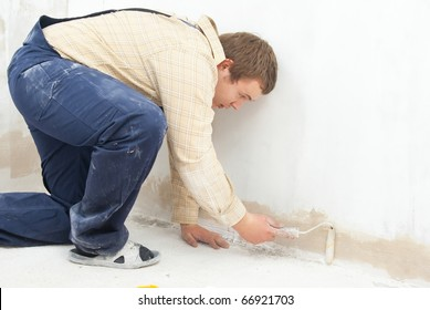 student worker paint wall with small roller