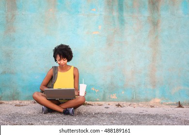 Student working with her laptop in the street