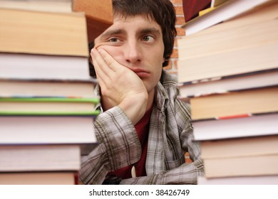 Student worried by number of books to read (man in focus)