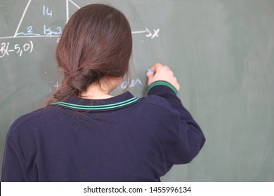 student writing at school on blackboard