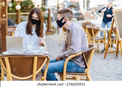 Jugendhipster-Mann und junge Frau in Gesichtsmasken trinken Kaffee in einem Café oder Restaurant im Freien. Neues normales Konzept nach Quarantäne-Konzept neu zu öffnen.