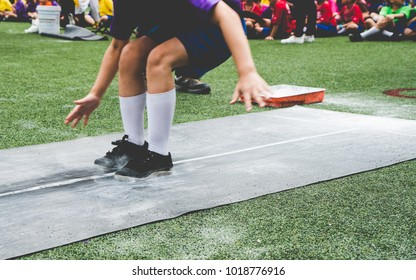 Students boy taking long jump on rubber board pid or sand pid during a school sport competition day. School sports day long jump competition (Focus on foots).