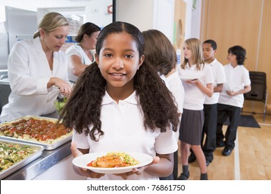 Students in cafeteria line with one holding up her healthy meal looking at camera