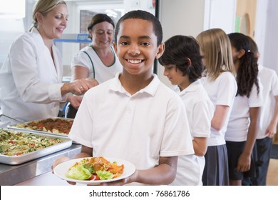 Students in cafeteria line with one holding his healthy meal and looking at camera