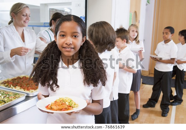 Students in cafeteria line with one holding her healthy meal and looking at camera