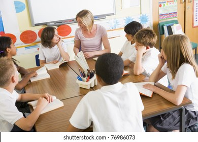 Students in class reading books with teacher