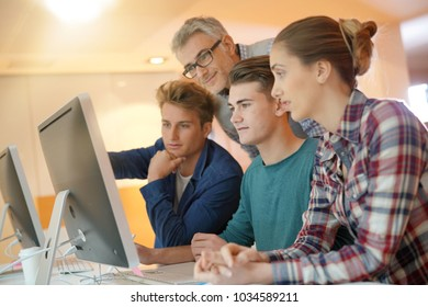 Students in class with teacher working on project