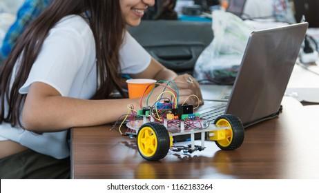 Die Schüler kodieren einen Roboter aus Metall und ein elektronisches Board. Robotik und Elektronik. Laboratorium. Mathematik, Ingenieurwesen, Naturwissenschaften, Technologie, Computercode. STEM-Ausbildung.