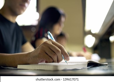 Students doing homework and preparing exam at university, closeup of young man writing in college library