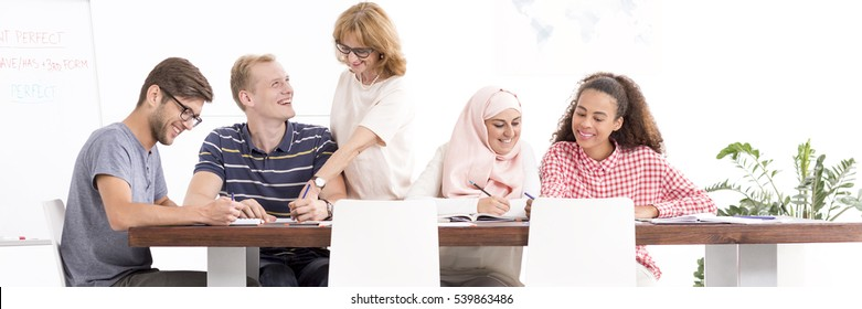 Students during language classes sit at the table and the teacher supervises their work