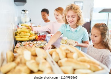 Students in elementary school pick up fruit at the buffet in the cafeteria