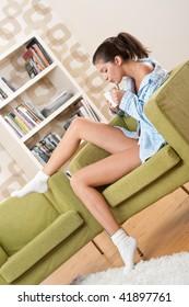 Students - Female teenager having cup of coffee, wearing pajamas in modern living room