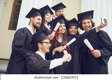 Students graduates are photographed on the phone at the university college.