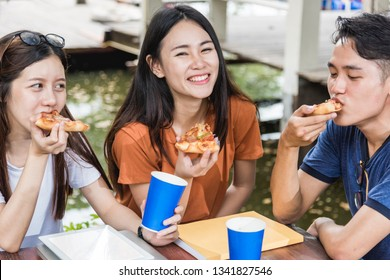 Students group woman and man eating pizza together with cheese delicious having fun and enjoy party at outdoor university, Education concept