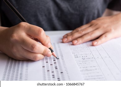 Students hand holding pencil writing selected choice on answer sheets and Mathematics question sheets. students testing doing examination. school exam