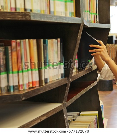 Students Hand Pick Up A Book From Bookshelf In The Library Selective Focus