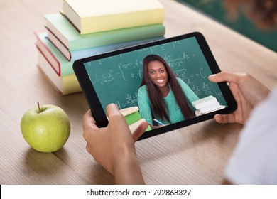Student's Hand Video Conferencing With Female Teacher On Digital Tablet