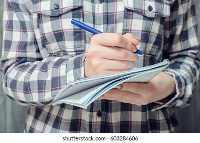 Student's hand writing in copybook, close-up photo