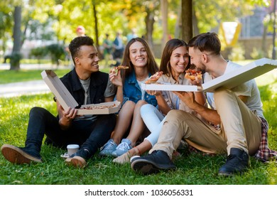 Students are having a lunch in the university campus. Two boxes of delicious pizza for hungry friends.