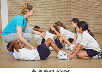 Students helping other students exercise at the elementary school