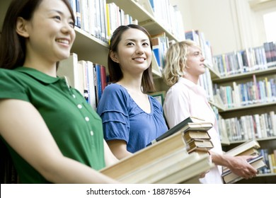 students holding book in library