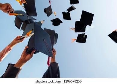 Schwarzer Hut der Absolventen, die am Himmel schweben.