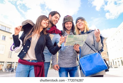 Students holding tour guide standing at city square at winter season - Happy group of university friends looking map under blue sky background - Concept of cheerful teenagers tourists on vacation