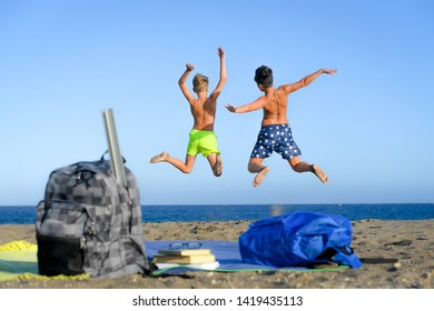 Students jumping happy on the beach celebrate the end of the school. Two excited boys playing together near the sea Concept of freedom and happiness. Schoolmates enjoying summer vacation taking bath