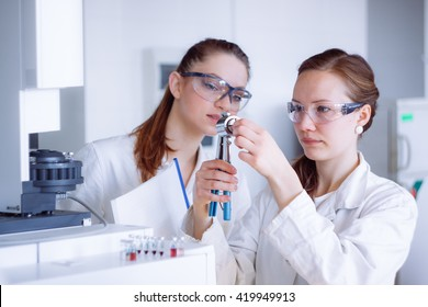 Students in lab. Chemist working with gas chromatograph.