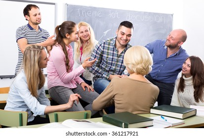 Students at language courses talking to a native speaker teacher during a break