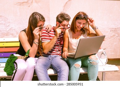 Students with laptop looking surprised by results of examinations - Three cheerful young best friends sharing news and web surfing - Modern concept of youth and communication - Marsala filter look