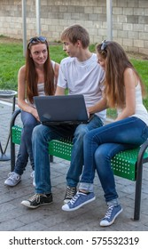 students with laptop outdoors