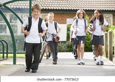 Students leaving school one with a bicycle