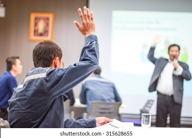 Students lifting hands in college class with teacher