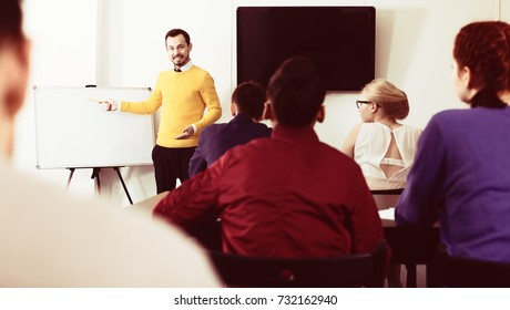 Students listening attentively to teacher explaining material during lesson in class