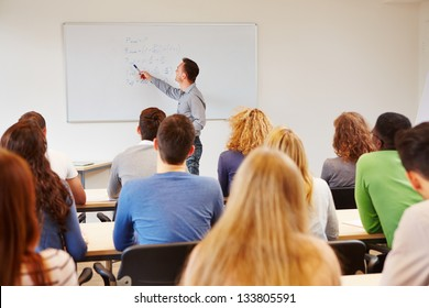 Students listening to teacher in class on a whiteboard