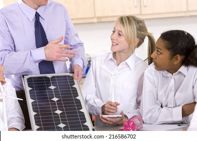 Students listening to teacher explaining solar panel and wind turbines in classroom
