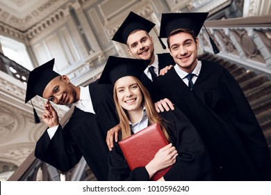 Students in mantles are happy that they finish their studies at the university. They are university graduates. They are very happy about this.