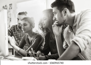 Students meet in front of a computer at the library to discuss the project they are working on. There's a hipster and a young black woman in the group. Black and white