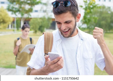 students with mobile phone or smartphone celebrating success