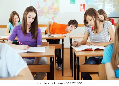 Students on exam, cute preteen boy cribbing from girl's notebook.