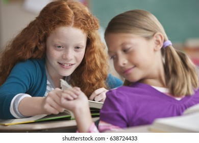 Students passing note in classroom