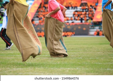 Students play running sack during sports day at school.