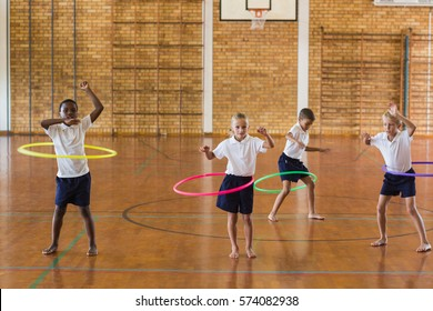 Students playing with hula hoop in school gym at elementary school